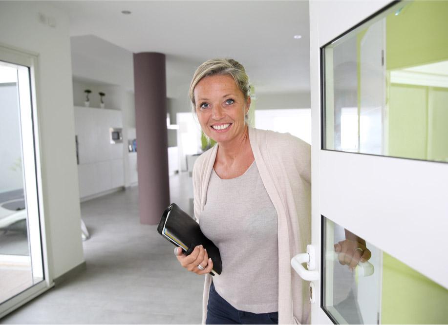 Smiley woman opening a door