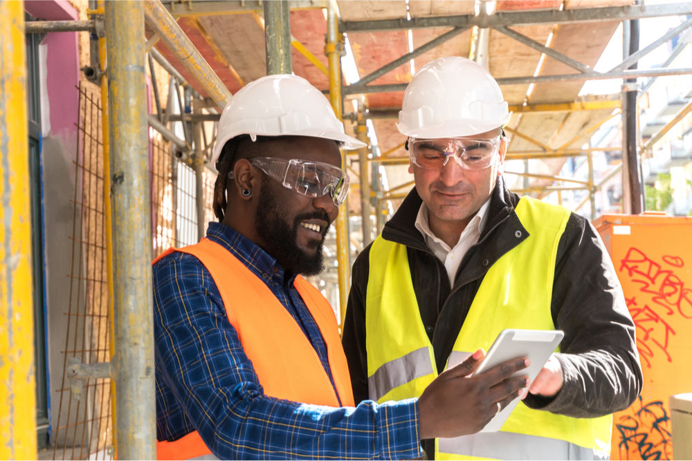 A worker and an engineer looking at a blueprint