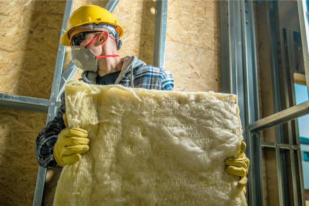 worker carrying a piece of thermal insulation